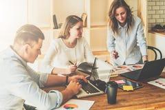 Группа в составе молодые люди работая совместно Человек использует компьтер-книжку, девушек смотря на экране компьтер-книжки, обс Стоковая Фотография
