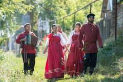 Группа в составе молодые люди в русских национальных костюмах идя вокруг деревни стоковое фото rf