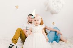 Группа в составе молодые люди, семья отца и матери 30 лет и дочь одного года, дома в светлом интерьере сидит на wo стоковая фотография