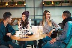 Группа в составе молодые люди сидя в кофейне Стоковые Изображения