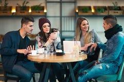 Группа в составе молодые люди сидя в кофейне Стоковая Фотография RF