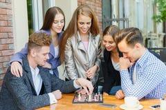 Группа в составе молодые люди в шахмат игры кафа стоковые фотографии rf