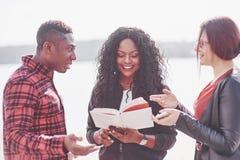 Группа в составе молодые многонациональные люди с книгой, студенты изучая на открытом воздухе стоковые фото