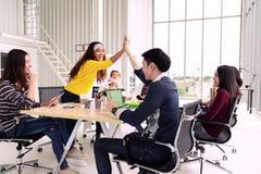 Группа в составе молодые многонациональные разнообразные люди показывать рука высоко 5, смеющся над и усмехающся совместно в встр стоковое фото