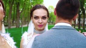Группа в составе молодые модели в одеждах свадьбы стоит все еще и представляет для камеры акции видеоматериалы