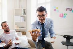 Группа в составе молодые мужские предприниматели имея обед в современном офисе стоковые фото