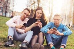 Группа в составе молодые подростки друзей используя чернь на улице города стоковая фотография