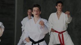 Группа в составе молодые поясы ног спортсменов босоногие, белые кимоно, красных и черных Зрачки тренируя южное и восточное смешан видеоматериал