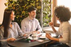 Группа в составе молодые предприниматели имея брифинг в кафе стоковое фото rf