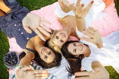Группа в составе молодые привлекательные женщины имея потеху в парке, лежа на траве Стоковые Изображения RF