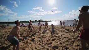 Группа в составе молодые привлекательные люди joyfully играет valleyball на солнечном пляже лета акции видеоматериалы