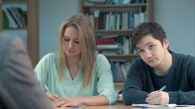 Группа в составе молодые студенты писать примечания в классе Стоковое Изображение RF