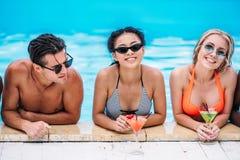 Группа в составе молодые счастливые многонациональные люди с коктеилями в заплывании Стоковые Фотографии RF
