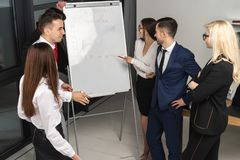 Группа в составе молодые уверенные люди bisiness анализируя данные используя доску офиса стоковое фото