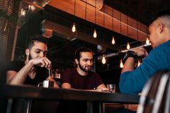 Группа в составе молодые человеки смешанной гонки говоря и смеясь над в ресторане Multiracial друзья имея потеху в кафе Пристанищ стоковые фото