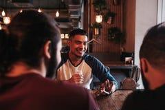 Группа в составе молодые человеки смешанной гонки говоря и смеясь над в Лаунж-баре Multiracial друзья имея потеху в кафе стоковое фото