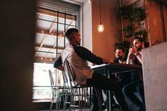 Группа в составе молодые человеки смешанной гонки говоря в Лаунж-баре Multiracial друзья имея потеху в кафе стоковые изображения rf