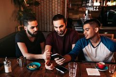 Группа в составе молодые человеки смешанной гонки используя телефон и говорящ в Лаунж-баре Multiracial друзья имея потеху в кафе стоковые изображения rf