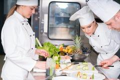 Группа в составе молодые шеф-повара prepairing еда в роскошном ресторане Стоковые Изображения RF