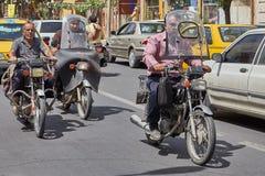 Группа в составе мотоцикл-велосипедисты едет вдоль улицы города, Kashan, Стоковая Фотография