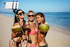 Группа в составе молодая женщина принимая selfie на пляже Стоковые Фото
