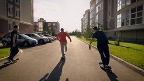 Группа в составе 3 молодого человека тренируя skateboarding совместно на улице видеоматериал