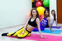 Группа в составе 3 молодой женщины сидя на поле в фитнес-клубе Стоковая Фотография RF