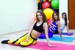 Группа в составе 3 молодой женщины сидя на поле в фитнес-клубе Стоковое Изображение