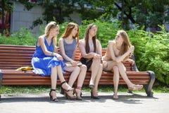 Группа в составе 4 молодой женщины сидя на стенде в парке лета Стоковое Изображение RF