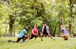 Группа в составе молодые бегуны протягивая и нагревая в парке Стоковое фото RF