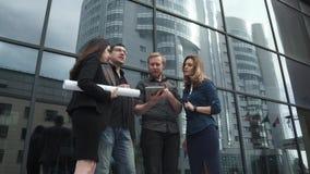 Группа в составе молодые бизнесмены говоря на предпосылке современного офисного здания сделанного из стекла Привлекательный челов сток-видео