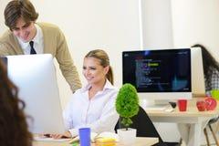 Группа в составе молодые бизнесмены имея потеху, ослабляя и работая в творческой комнате Стоковые Изображения RF