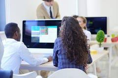 Группа в составе молодые бизнесмены имея потеху, ослабляя и работая в творческом космосе комнаты Стоковое фото RF