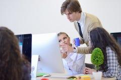 Группа в составе молодые бизнесмены имея потеху, ослабляя и работая в творческом космосе комнаты Стоковые Изображения