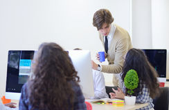 Группа в составе молодые бизнесмены имея потеху, ослабляя и работая в творческом космосе комнаты Стоковые Изображения RF