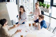 Группа в составе молодые бизнесмены обсуждая новый проект на деловом совещании мелкого бизнеса Стоковое фото RF