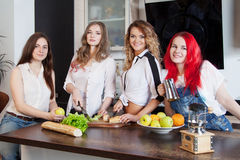 Группа в составе молодые женщины в подготавливать комнаты кухни Стоковое Фото
