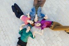 Группа в составе молодые женщины держа руки совместно изолировала лежать на th Стоковая Фотография RF