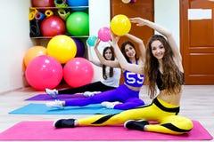 Группа в составе молодые женщины держа шарики сидя на поле в fitnes Стоковая Фотография