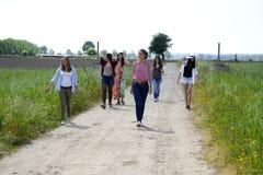 Группа в составе молодые женщины идя на поле wildflowers Стоковая Фотография RF