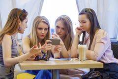 Группа в составе молодые женщины сидя вокруг таблицы есть десерт Стоковая Фотография
