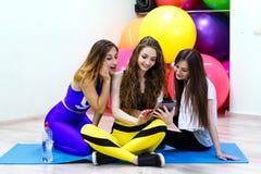 Группа в составе молодые жизнерадостные кавказские женщины используя ПК таблетки в пригонке Стоковые Изображения