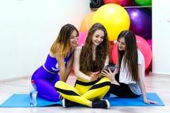 Группа в составе молодые жизнерадостные кавказские женщины используя ПК таблетки в пригонке Стоковая Фотография RF