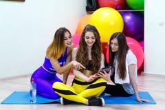 Группа в составе молодые жизнерадостные кавказские женщины используя ПК таблетки в пригонке Стоковые Фото