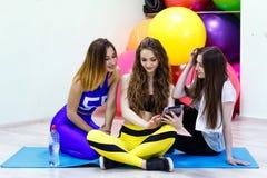 Группа в составе молодые жизнерадостные кавказские женщины используя ПК таблетки в пригонке Стоковые Фотографии RF