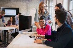 Группа в составе молодые дизайнеры перспективы обсуждая в офисе Стоковые Изображения