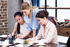 Группа в составе молодые коммерсантки работая совместно на таблице с бумагами Стоковые Фотографии RF
