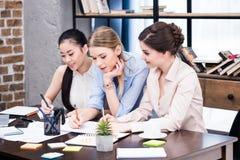 Группа в составе молодые коммерсантки работая совместно на таблице с бумагами Стоковые Изображения RF