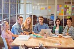 Группа в составе молодые коллеги используя компьтер-книжку Стоковые Изображения