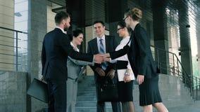 Группа в составе молодые предприниматели встречая около делового центра и приветствуя один другого сток-видео